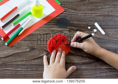 Child Draws Items On The Paper Blank. The Child Makes A Postcard With Ladybird. Glue, Paper, Scissor