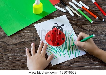 Child Draws Items On A Paper Card. The Child Makes A Postcard With Ladybird. Glue, Paper, Scissors O