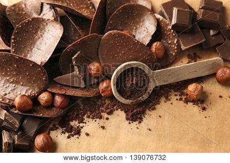 Chocolate chips and spoon with cocoa powder on parchment background