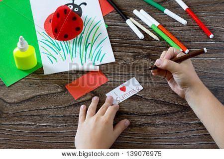 Child Paper Writes That The Details I Love Summer. The Child Makes A Postcard With Ladybird. Glue, P