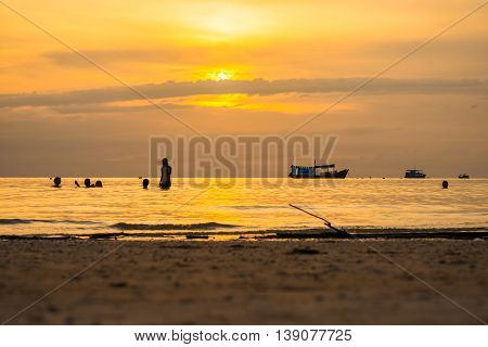 The Beautiful Silhouette Evening Sunset With People On Beach At The Sea