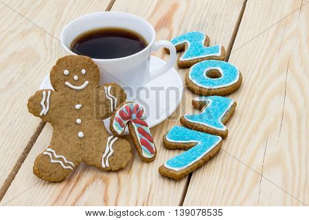Homemade gingerbread cookie man with numerals 2017 and cup of coffee on wooden table