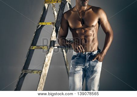 African Male Model Leaning Against A Ladder In Jeans.
