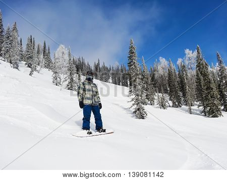 A snowboarder stands on a steep mountain on a clear Sunny day. looking at the camera
