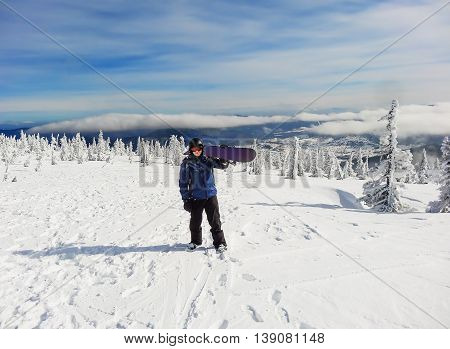 A snowboarder with a snowboard stands on a steep mountain on a clear Sunny day. looking at the camera