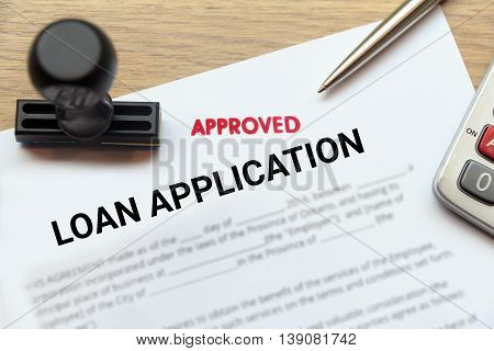 Approved loan application form lay down on wooden desk with rubber stamp and calculator.