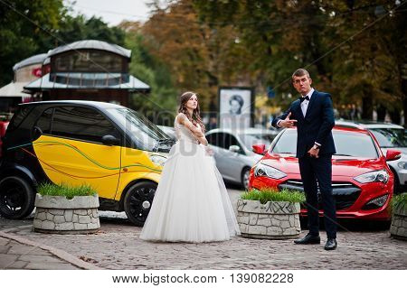 Modern Newlyweds Having Fun On Streets Of City Background Colored Cars