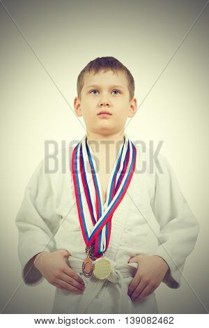 Karate Boy In White Kimono With Medals Fighting