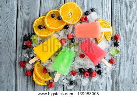 Variety of healthy ice popsicles with fruits and berries on ice top view