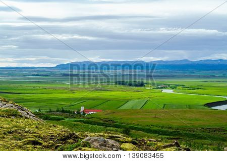 Small village with horses grazing in the green field at Iceland landscape