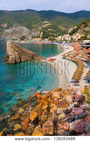 Monterosso Italy - July 02 2016: beach scene in Monterosso al Mare with unidentified people. Monterosso is one of the famous five UNESCO protected picturesque towns in the Cinque Terre