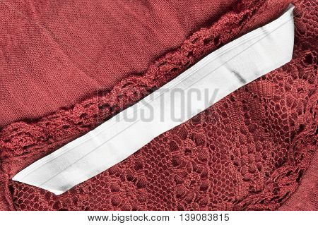Blank clothes label on red lace as a background