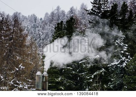 Smoke from chimney on roof rising in the air Winter time from europe
