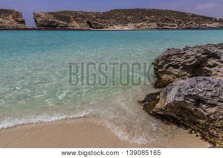 Rocks close to turquoise bright sea in Malta island