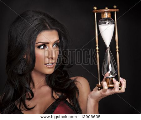 woman holding an hour glass timer