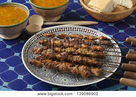 Moroccan lamb kebab on a table with bread and harira soup