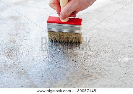 Coating the concrete floor with a brush