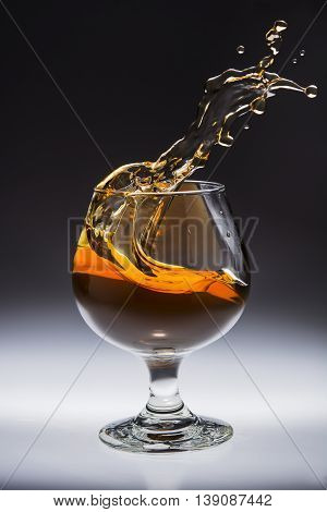 Amber alcoholic drink splashing in a glass