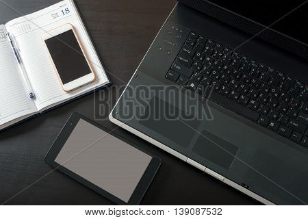 Laptop, tablet, mobile phone, notebook, lying on a black table