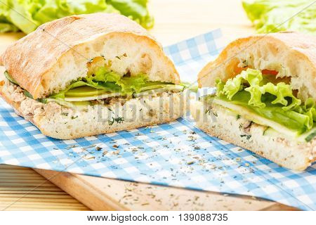 Large ciabatta sandwich with tuna, green, apple and cucumber lying on a blue napkin and a wooden board