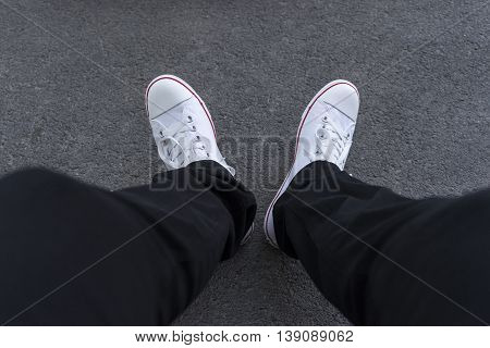 Men's feet in black trousers and white sneakers on the pavement