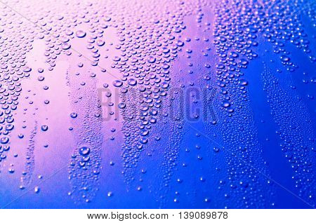 Colorful background with condensed water drops close up