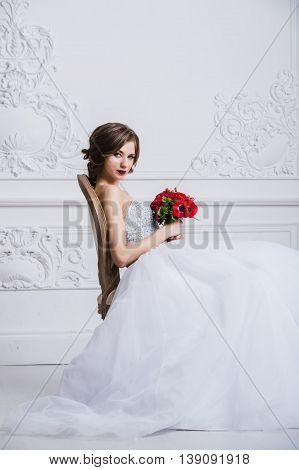 Woman in white dress sitting on antique vintage chair. Looking at camera and smiling. Turned aside with flowers in her hands