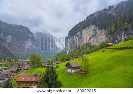 Aerial view of Lauterbrunnen Valley with waterfall from high cliff in Background - Switzerland