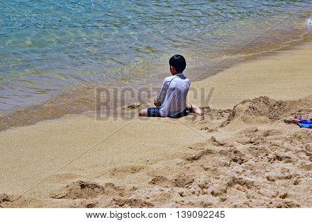 A boy watches the waves, Hanauma Bay, Hawaii