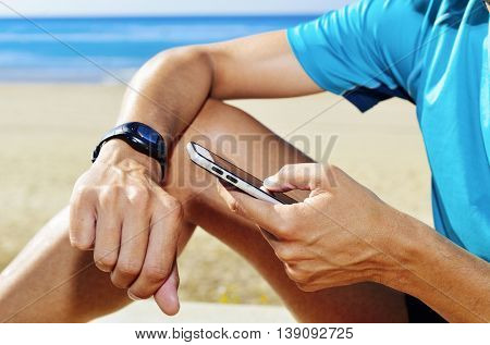 closeup of a young man wearing sport clothes syncing his smartphone and his smartwatch
