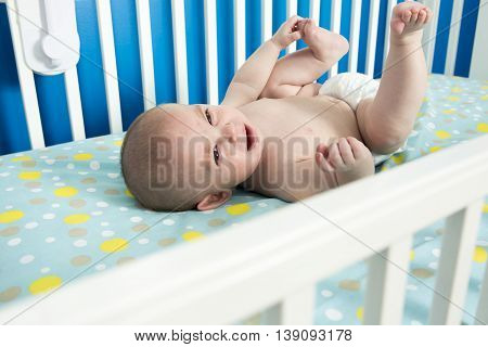 A cute one month old newborn baby is laying on her back in the crib, crying.