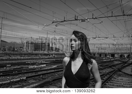 Beautiful young brunette with long hair posing along the railroad tracks