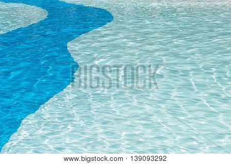 crystal clear cool swimming pool background with sun reflection ripples in a two tone blue solid curve pattern ideal for ad poster copy space or text