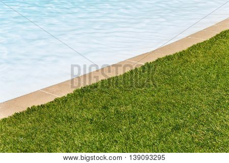 Clear and natural Grass edge swimming pool background with half and half grass and pool ideal for a poster ,background, copy space
