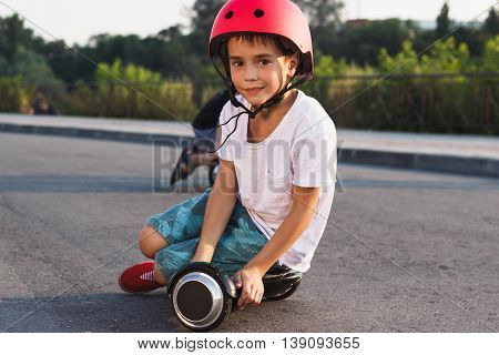 Boy Sits On The Black Gyro Scooter Outdoors