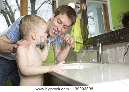 A Father and son brushing teeth in bathroom