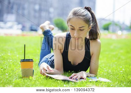Young brunette woman reading magazine lying on green grass