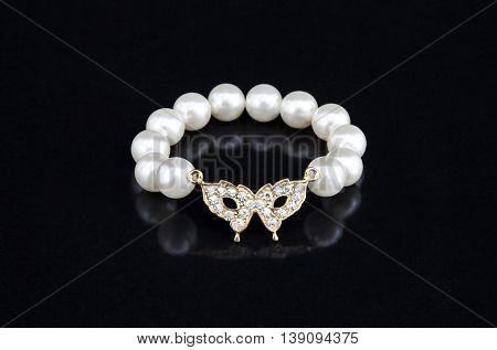 Pearls bracelet in a black mirror reflex