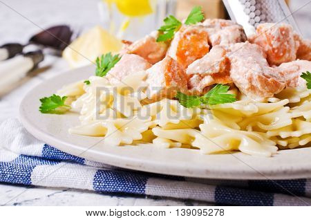 Pasta farfalle with salmon and parsley. Selective focus.