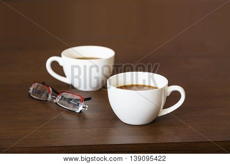 Cups Of Hot Coffee On Wooden Table