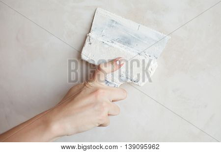 Woman hand with manicure. Closeup of palette-knife or scraper and cement filling for house renovation construction.