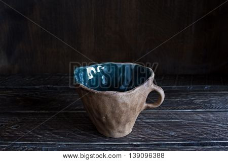 brown clay cup with teal glaze inside clay cup handmade
