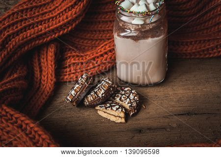 Cup with cocoa and marshmallows chocolate chip cookies and orange scarf