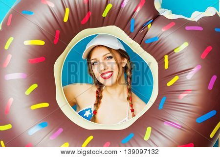 Closeup portrait of cute young woman with brown sprinkled doughnut float against blue background. Beautiful teenage girl with braided hair, donut float. Vibrant colors, medium retouch.