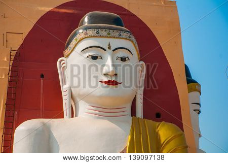 The Buddha Is Face Closeup. Four Statues Of Sitting Buddhas. Pagoda Kyaikpun Buddha. Bago, Myanmar.