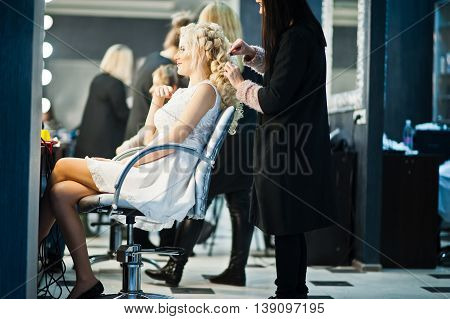 Hairdresser coiffeur makes hairstyle of gentle blonde bride