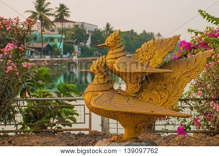 Two Gold Sculptures Of Birds. One Bird Sits On The Other. Bago In Myanmar. Burma.