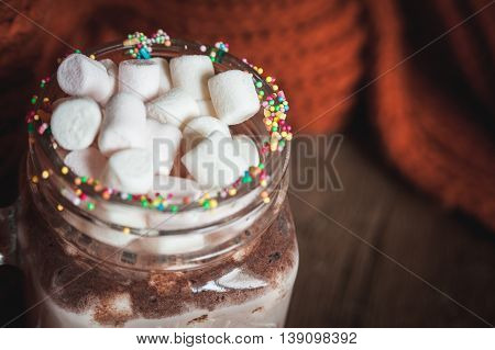 Marshmallows in glass with cocoa on the background of knitted orange scarf