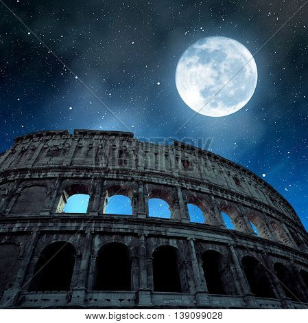 Flavian Amphitheatre or Colosseum in Rome with night sky and moon in the background, Italy.