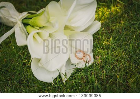 Wedding rings with calla bouquet. wedding bouquet of flowers calla and two golden rings. Bridal bouquet and wedding rings